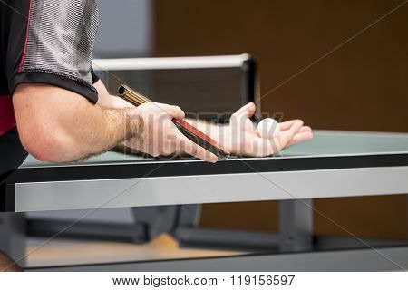 table tennis player serving - focus at the players hand/blade / small depth of focus