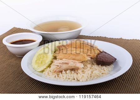 Hainanese chicken rice, steamed chicken, chicken blood and white rice on brown cloth background.