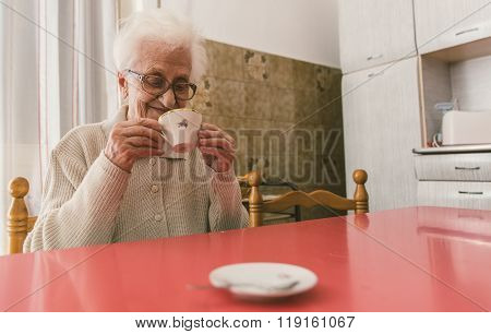 Old Woman Drinking A Coffee In The Kitchen