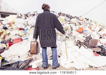 Homeless Standing In Front Of A Plastic Mountain