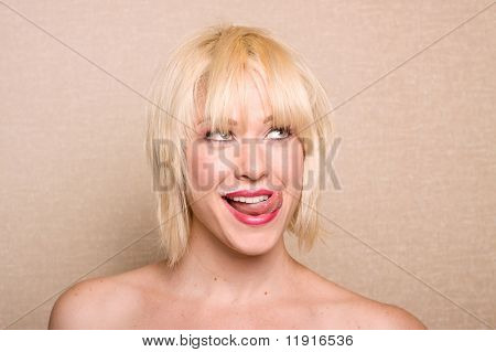 Beautiful woman sticking her tongue out after drinking milk