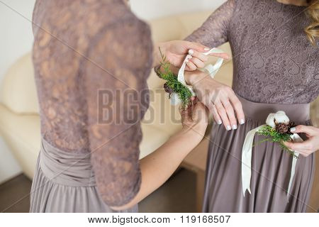 bride putting boutonniere on bridesmaid's hand in indoor