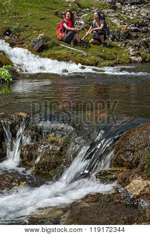 Flow of transparent pure mountain creek water and people on background