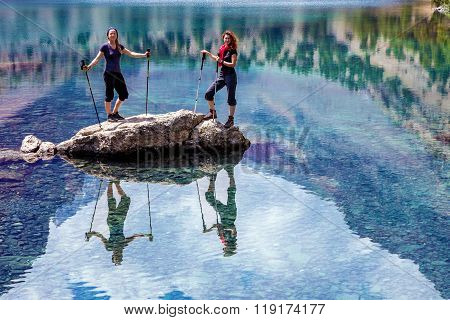 Two smiling females staying Amidst Blue Mountain Lake