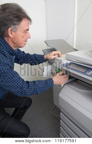 Frustrated Man Opening Photocopy Machine Trying To Fix Problem