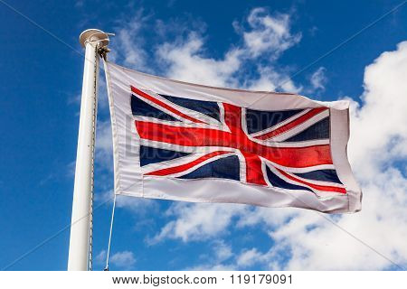 Union Jack Flag on a flag pole blowing in the wind.
