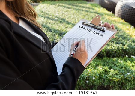 Businesswoman Signing A Car Insurance Policy On The Street