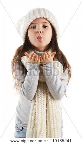 Little girl in trendy knitted clothes making air kiss, isolated on white