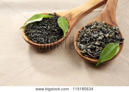 Dry tea with green leaves in wooden spoons on beige background