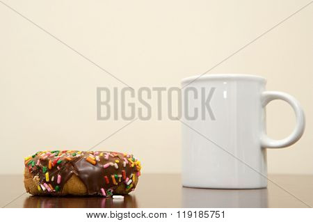 Coffee cup and doughnut on a desk