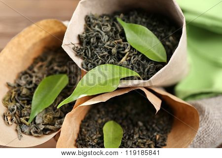 Dry tea with green leaves in cornets, closeup