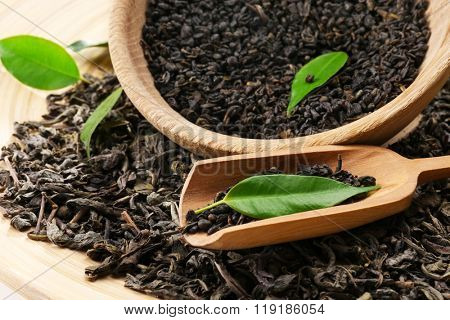 Dry tea with green leaves in wooden utensil, close up