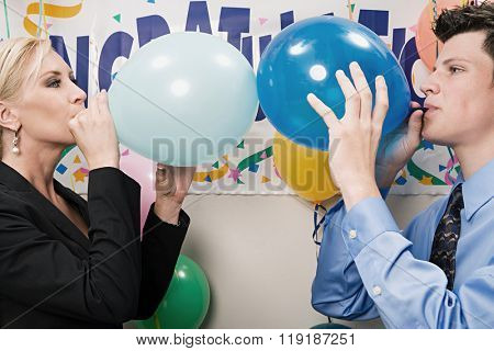 Two office workers blowing up balloons