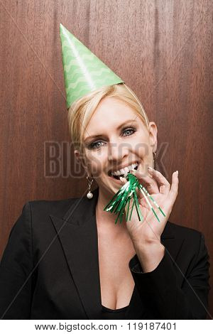 Businesswoman blowing party horn blower
