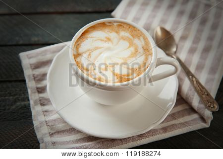Cup of hot cappuccino with froth and spoon on a black wooden table