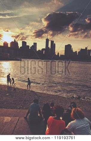 NEW YORK - CIRCA SEPTEMBER 2015: Sunset over New York City from the shores of the East River with people sitting on steps and frolicking in the water watching the sun go down