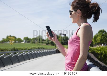 Woman Reading Phone In Park