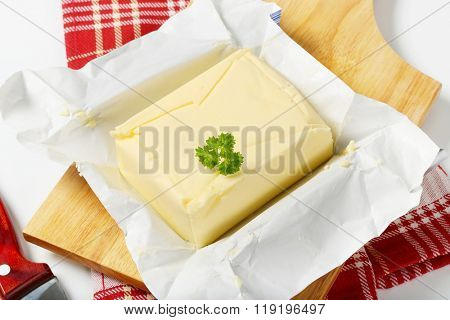 block of fresh butter on wooden cutting board - close up