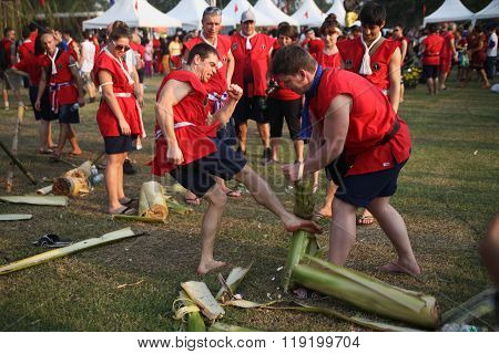 AYUTTHAYA,THAILAND - MARCH 17,2013:  Two young adult caucasian Muay Thai fighter breaks tree trunk on training.