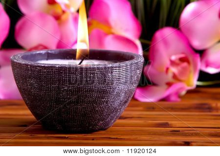 Spa candle and orchid on bamboo mat