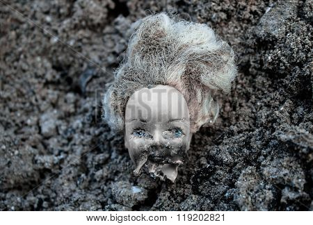 Plastic Scald Doll Head Lying In A Pile Of Dirt