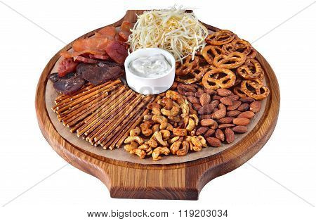 Mix Of Beer Snacks On Round Wooden Board