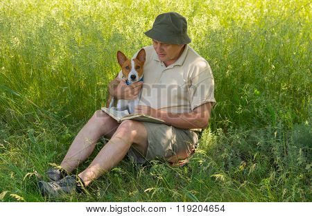Man reading to young dog interesting book under a tree shadow at spring season
