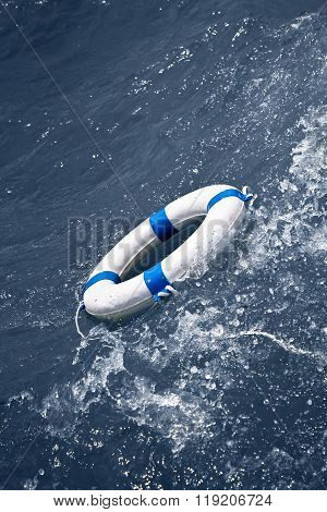 White Lifebuoy Floating In A Storm Ocean Wave