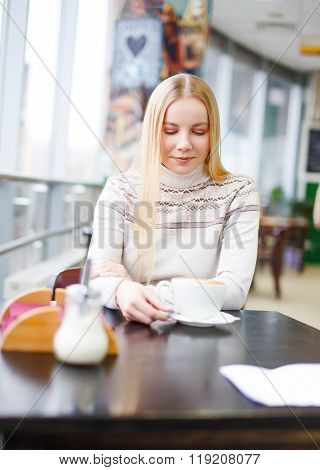 beautiful blonde girl is drinking coffee in a cafe