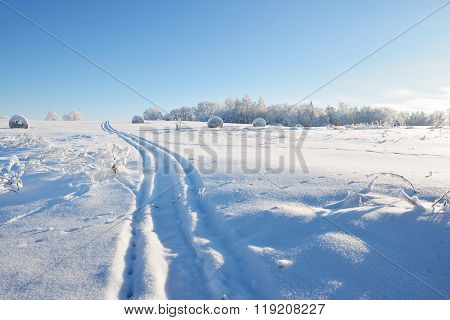 Tracks On A Snowcovered Field With Hay Bales