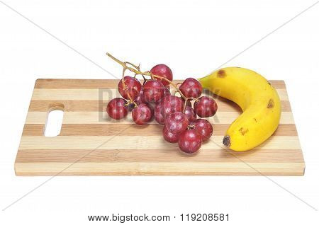 Delicious Bunch Red Seedless Crimson Grape And Banana On Bamboo Chopping Board Isolated On White