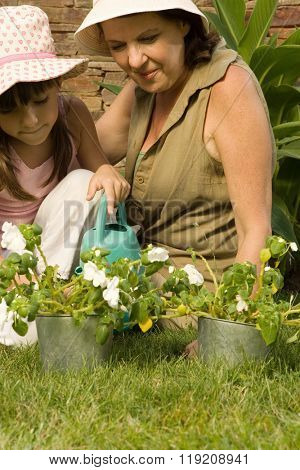 Girl and grandmother watering plants