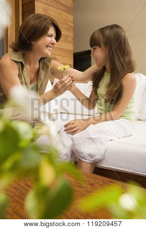 Girl giving flower to grandmother