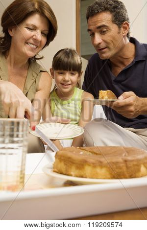 Girl having cake with grandparents