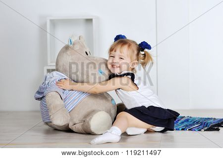 Little girl hugging a teddy hippo in studio