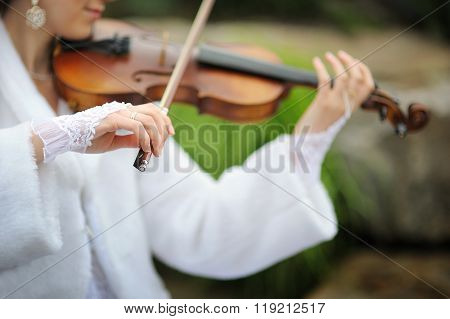 Bride playing on violin for groom in summer park