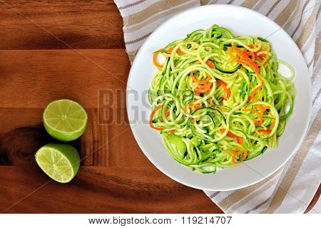 Zucchini noodle dish with lime on wood background