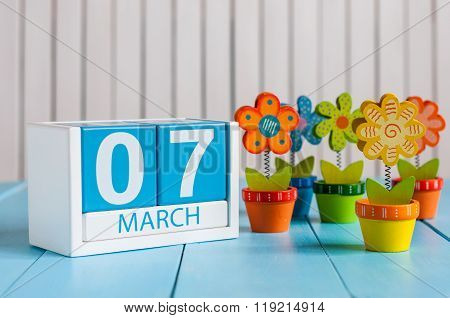 March 7th. Image of march 7 wooden color calendar with flower on white background.  First spring day