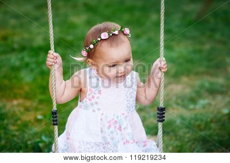 Adorable baby girl wearing white dress enjoying swing