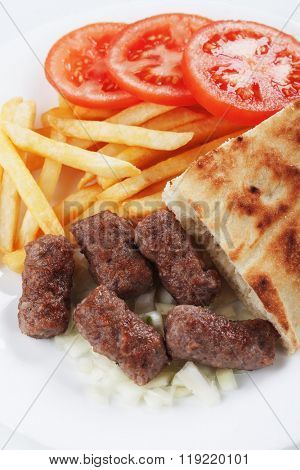Cevapcici, bosnian minced meat kebab with somun bread and french fries