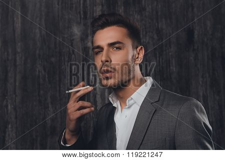 Handome Sexy Man In Suit On The Grey Background Smoking A Cigarette