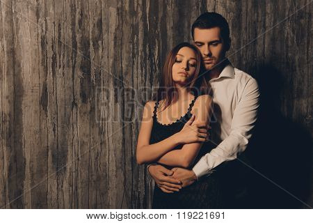 Handsome Man Embracing  His Sexy Woman Near Dark  Wall