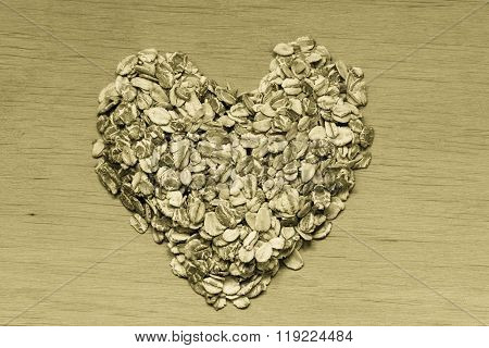 Oat Flakes Cereal Heart Shaped On Wooden Surface.