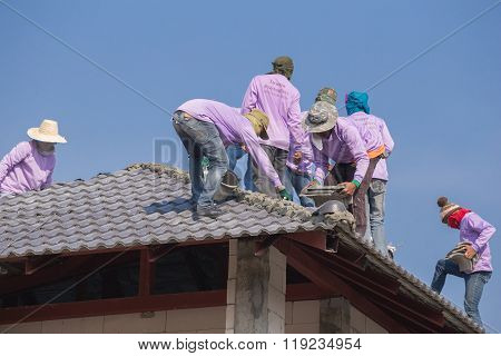 Construction Workers Installing Roof Tiles For Home Building