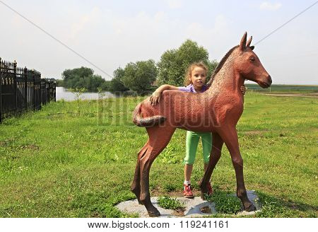 Little girl and sculpture foal. Tourist Complex Siberian Podvorye.