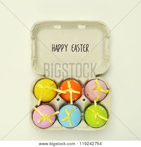 high-angle shot of an egg carton full of decorated easter eggs of different colors and the text happy easter written in it