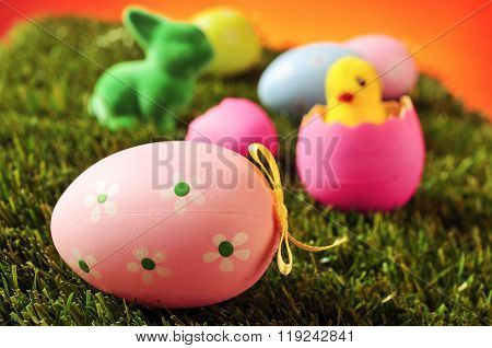 closeup of a pink decorated egg on the grass with some other colorful decorated eggs, a green easter rabbit and a toy chick emerging from a pink egg in the background