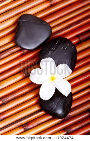 Hot spa stones and tropical frangipani flower on bamboo mat