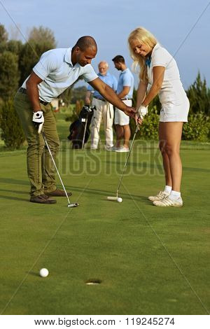 Pretty female golfer learning putting on the green.