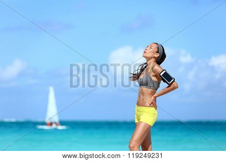 Tired jogging woman catching her breath taking a break of hard workout. Young Asian female athlete runner holding her back in pain after intense cardio running exercise on long beach run.